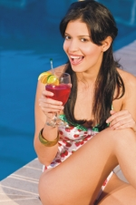 woman sipping cocktail by pool
